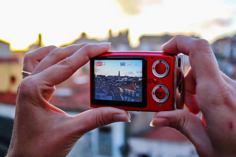Cropped hands photographing town through camera