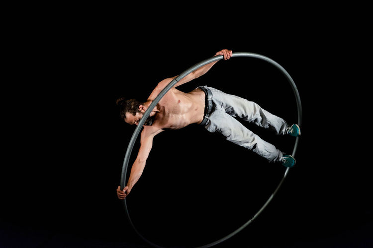 Circus Acrobat Adult Agility Arms Raised Arts Culture And Entertainment Balance Black Background Dancing Effort Exercising Flexibility Full Length Gymnastics Healthy Lifestyle Human Arm Indoors  One Person Performance Skill  Sport Sports Clothing Strength Studio Shot Vitality