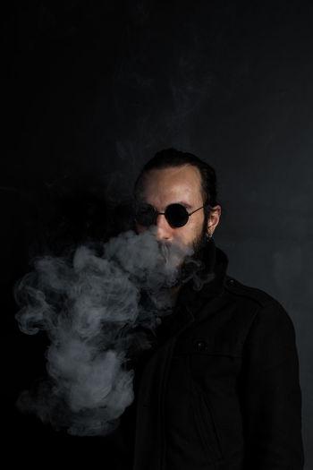 Man exhaling smoke against gray wall