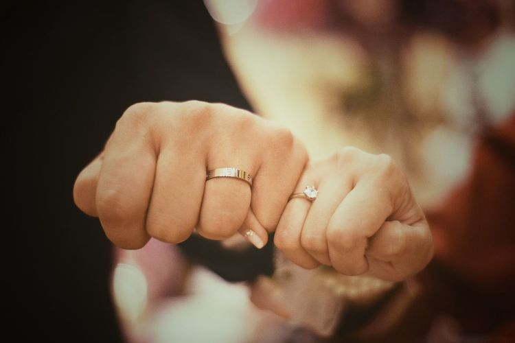 Close-up of wedding couple showing rings
