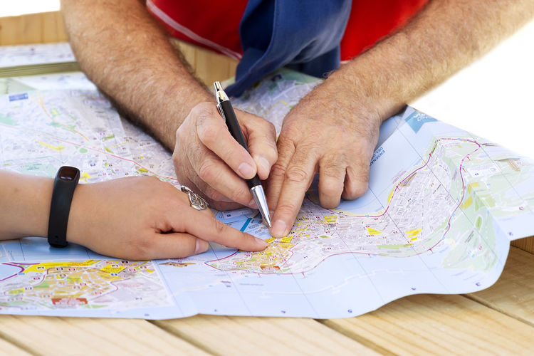tourists consulting local map guide on city street City Map Map Planning Tourist City Guide Close-up Creativity Guide Hand Human Body Part Human Hand Leisure Activity Map Men Pen People Real People Table Tourism Tourist Destination