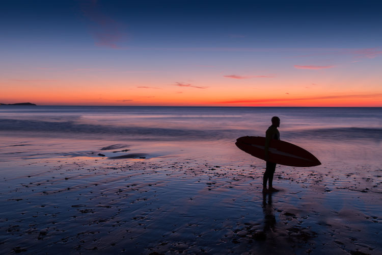 Silhouette Of Surfer Standing On Beach At Sunset