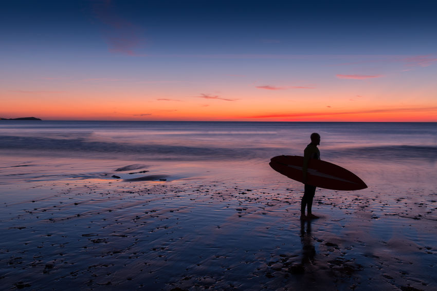 Surfer on beach at sunset Atlantic Ocean Beach Cornwall Landscape Man Nature Newquay One Man Only One Person Sea Silhouette Sunset Surfboard Surfer Water Watergate Bay Fresh On Market 2017