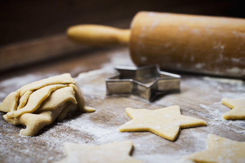 Close-up of star shape cookies and rolling pin with cutter on table