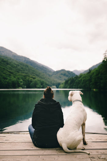 Woman with dog sitting on the dock and looking at river