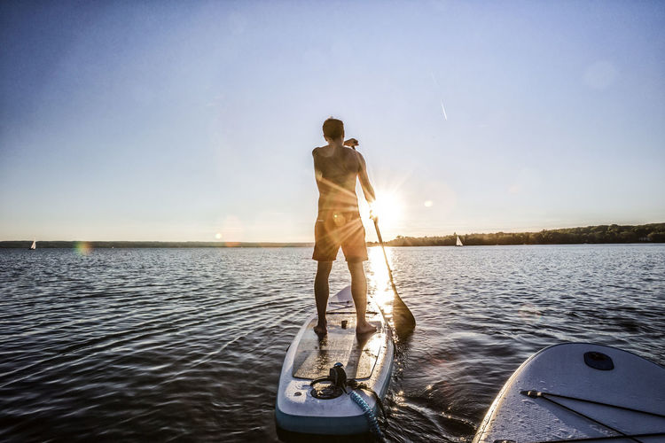 Man paddleboarding in sea against clear sky