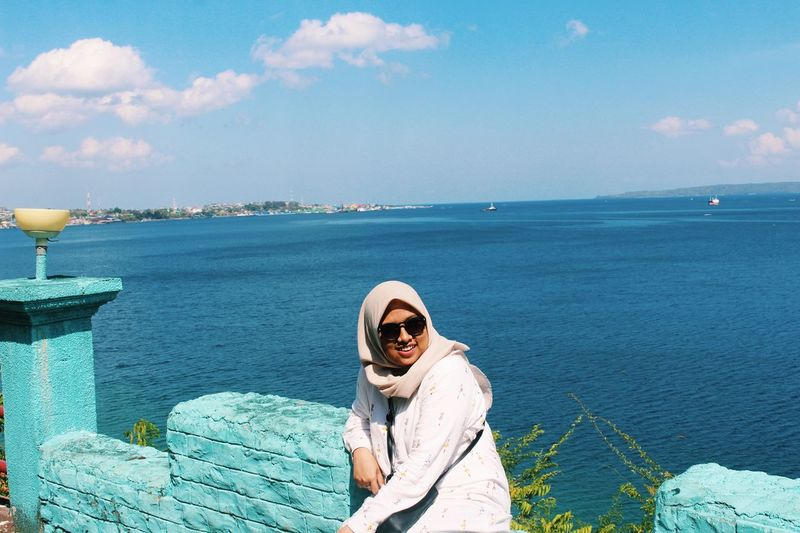High angle view of young woman in hijab wearing sunglasses while sitting against sea during sunny day