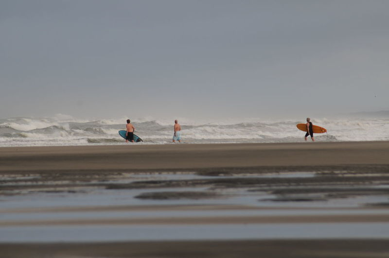 People walking on shore at beach against sky