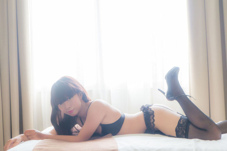 Portrait Of Beautiful Seductive Woman Lying On Bed Against Window At Home