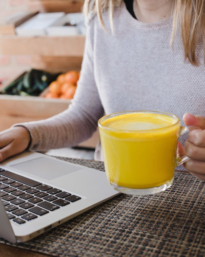 Technology Drink Food And Drink Adult Communication Midsection Wireless Technology Holding One Person Connection Casual Clothing Sitting Lifestyles Women Human Hand Computer Hand Refreshment Cup Using Laptop Glass Orange Color