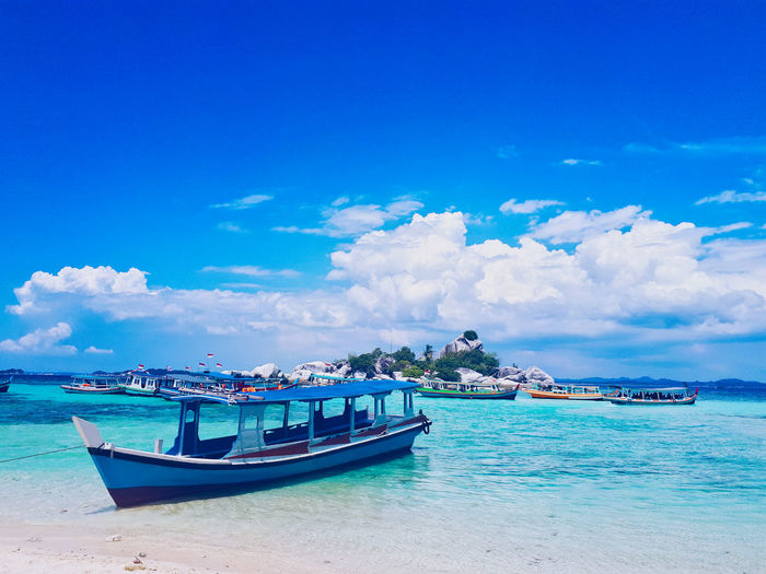 Hidden Paradise in Bangka . Bangka, Indonesia. Nautical Vessel Sky Transportation Water Sea Mode Of Transportation Cloud - Sky Blue Scenics - Nature Nature Day Beauty In Nature Beach Waterfront Moored Land Travel Incidental People Horizon Over Water Outdoors Turquoise Colored Fishing Boat Nature Beauty In Nature EyeEm Selects