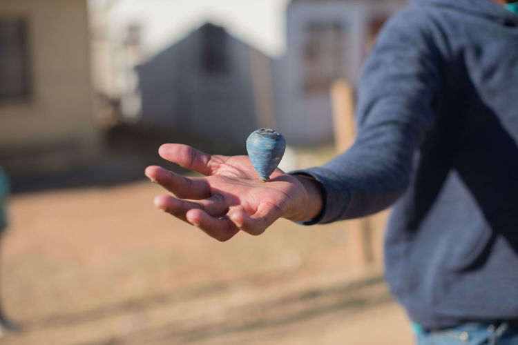 Midsection of man holding spinning top
