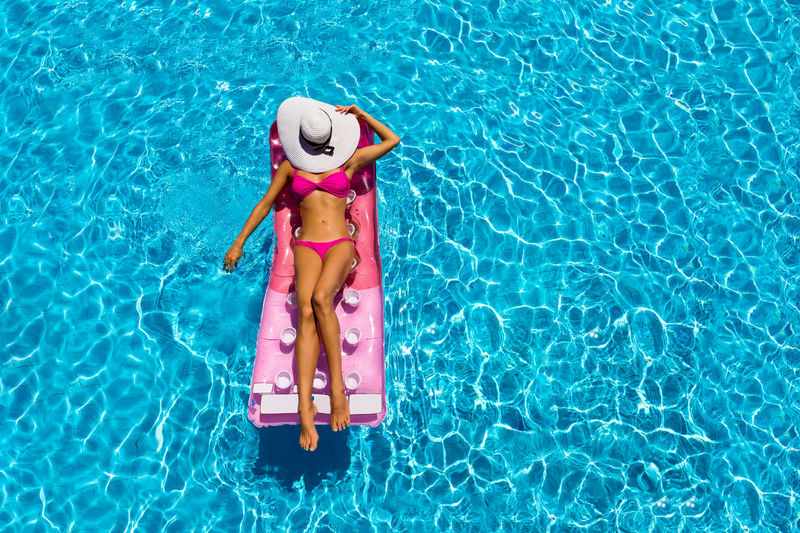 Attractive woman is relaxing in the pool, aerial view Hat Holiday Relaxing Vacations Woman Aerial View Attractive Bikini Floating Floating On Water Girl Leisure Activity Lifestyles Model One Person Pink Color Real People Sexygirl Sleeping Summer Sun Sun Hat Swimming Pool Vacations Water