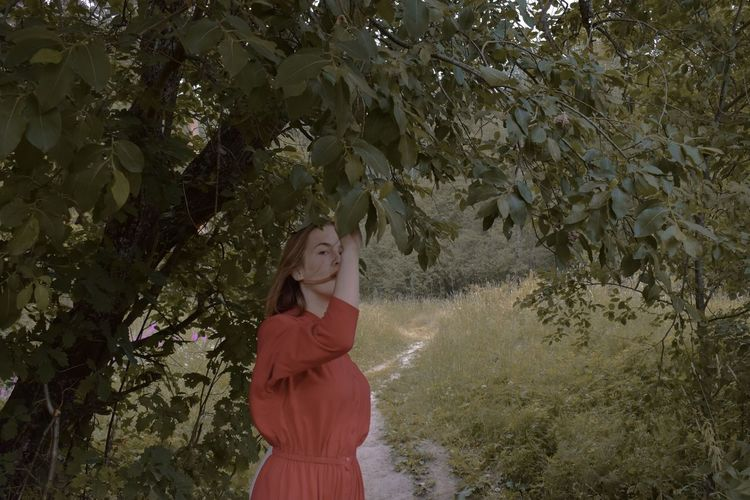 Young woman standing by tree against plants