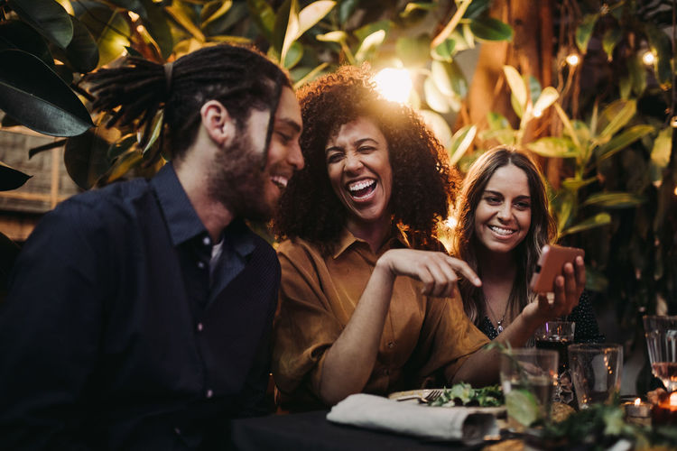 Cheerful friends while sitting at table in restaurant