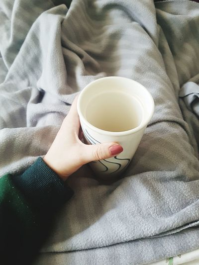 High angle view of hand holding coffee cup on bed warming up with hot drink