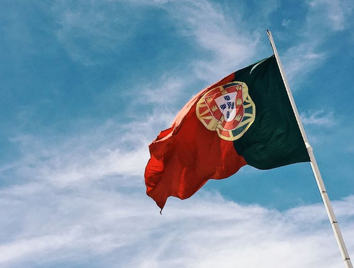 Low angle view of portuguese flag waving against blue sky