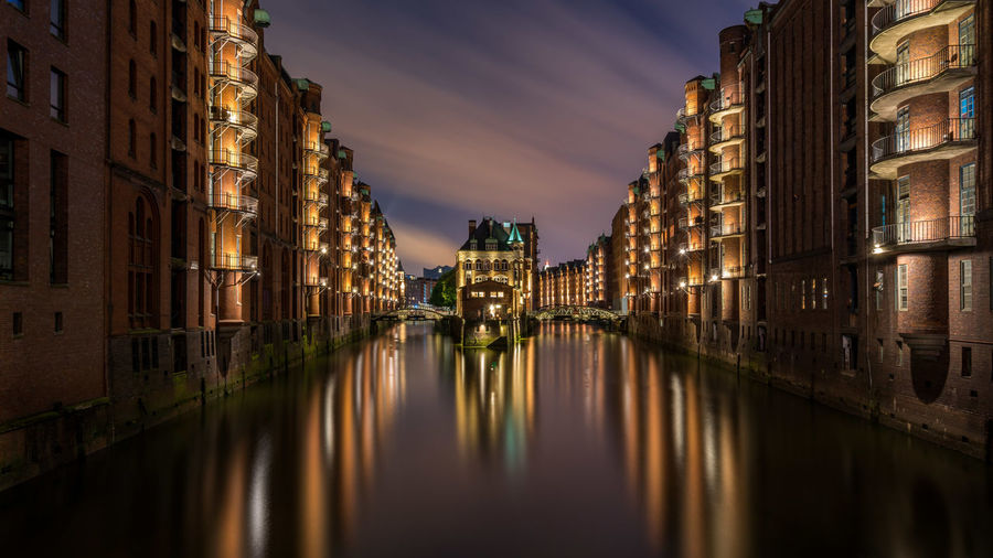 Canal passing through city at night