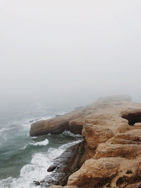 Fog rolling over a coastal cliff on the Oregon coast Sea Water Beauty In Nature Scenics - Nature Sky Beach Rock Nature Land Tranquil Scene No People Day Wave Tranquility Rock - Object Motion Solid Non-urban Scene Idyllic Outdoors