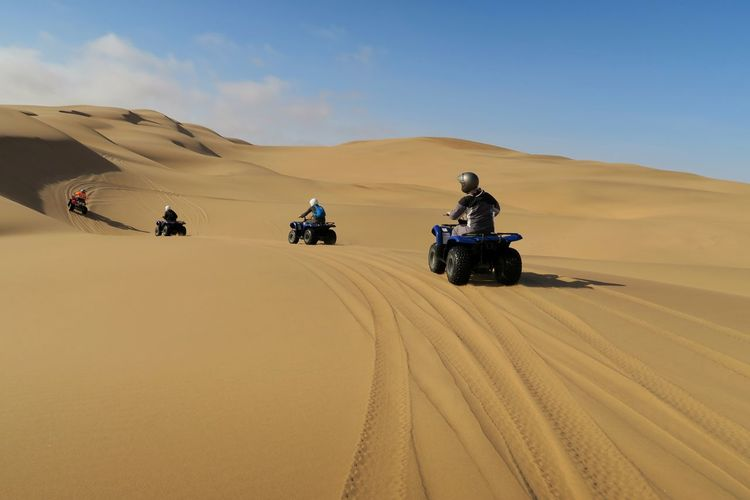 People riding off-road vehicles in the desert