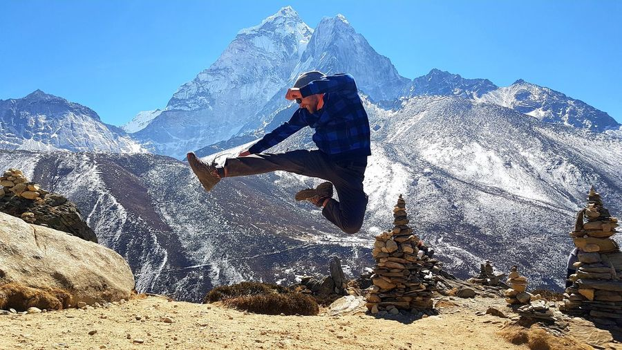 Full length of man jumping against snowcapped mountains
