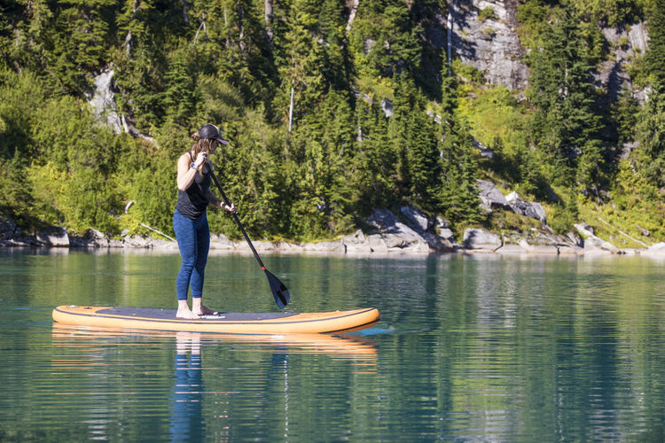 Full length of man standing on lake in forest