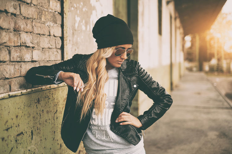 Fashionable Young Woman Wearing Jacket Smoking Cigarette Outdoors
