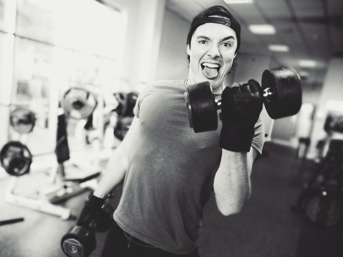 Portrait Of Man Lifting Dumbbells In Gym