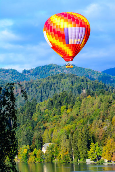 Hot Air Balloon Balloon Air Vehicle Transportation Mid-air Flying Mountain Adventure Nature Sky Water Mode Of Transportation Scenics - Nature Beauty In Nature Tree Plant Non-urban Scene Ballooning Festival Multi Colored Outdoors No People