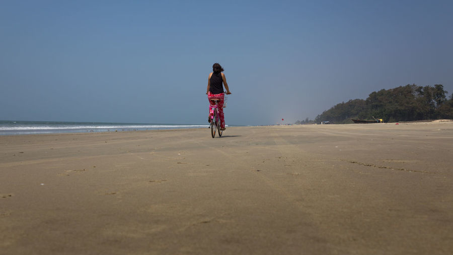 Rear view of woman riding on beach