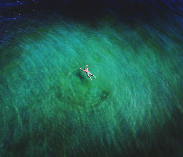 High angle view of shirtless man floating on sea