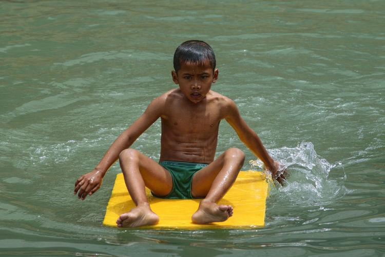 Shirtless Boy Playing In Lake