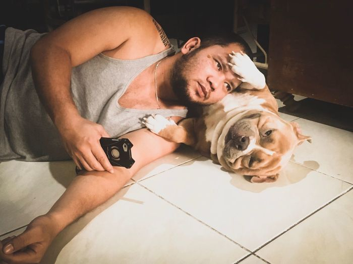 Man With Dog Lying Down On Floor At Home