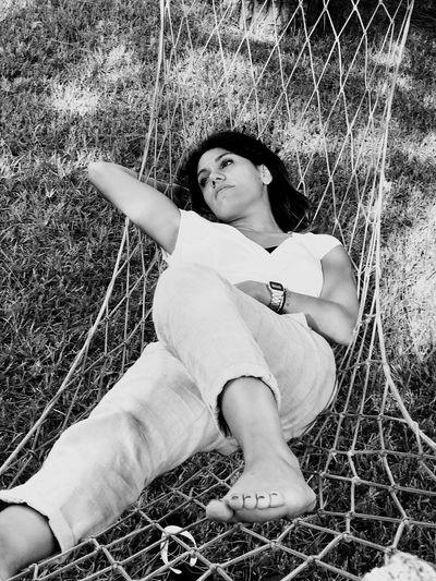Woman Relaxing On Hammock Over Field