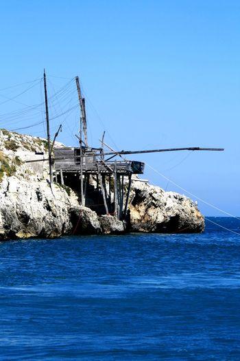 Sailboat on sea against clear blue sky