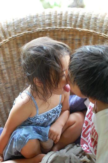 Playful siblings on wicker seat