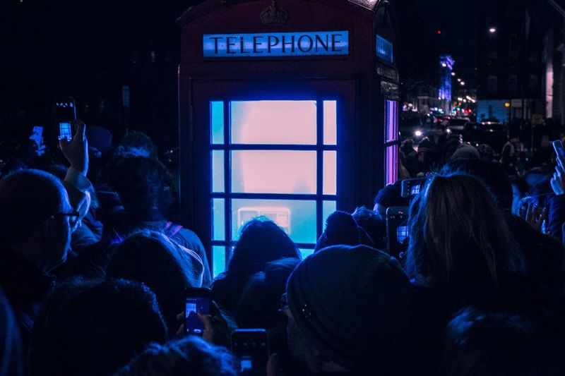 People photographing illuminated telephone booth at night