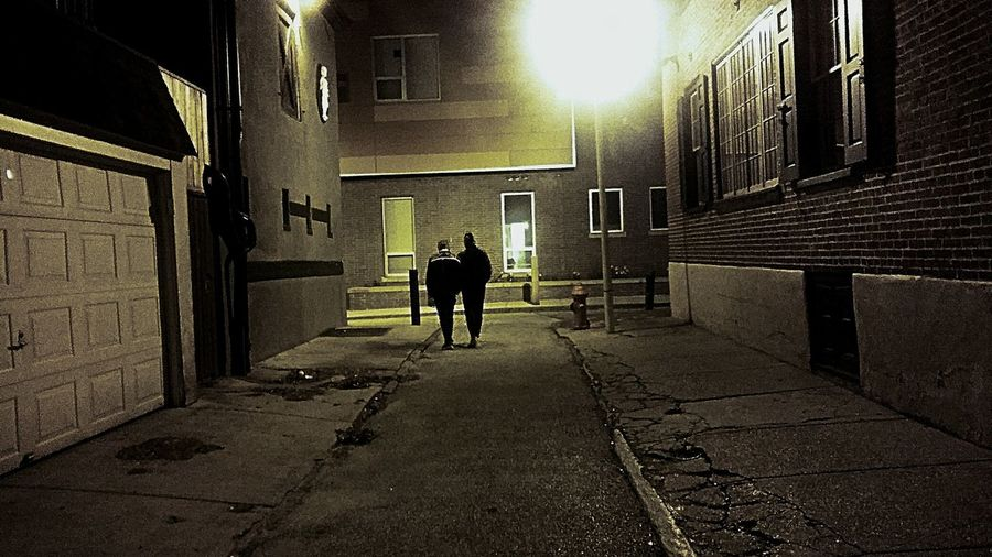 Rear view of silhouette people walking on street at night