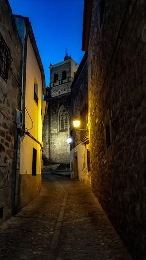 Narrow alley along buildings at night
