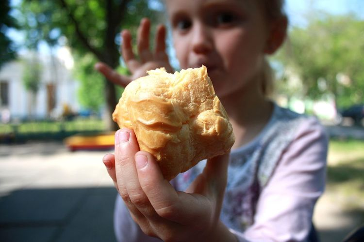 Close-up of girl holding bread outdoors