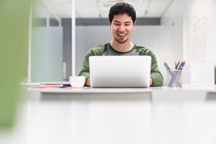 Cheerful businessman working on laptop