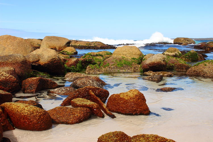 View of rocks in sea against sky
