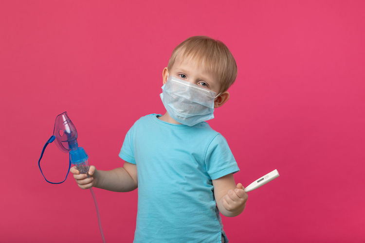 A blond child with an inhaler and a thermometer in his hand on a plain pink background. studio.