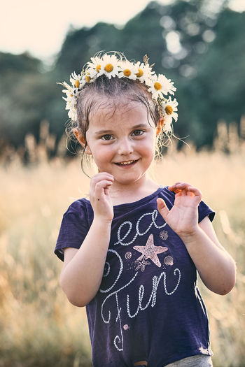 Portrait of smiling girl wearing flowers while standing on land