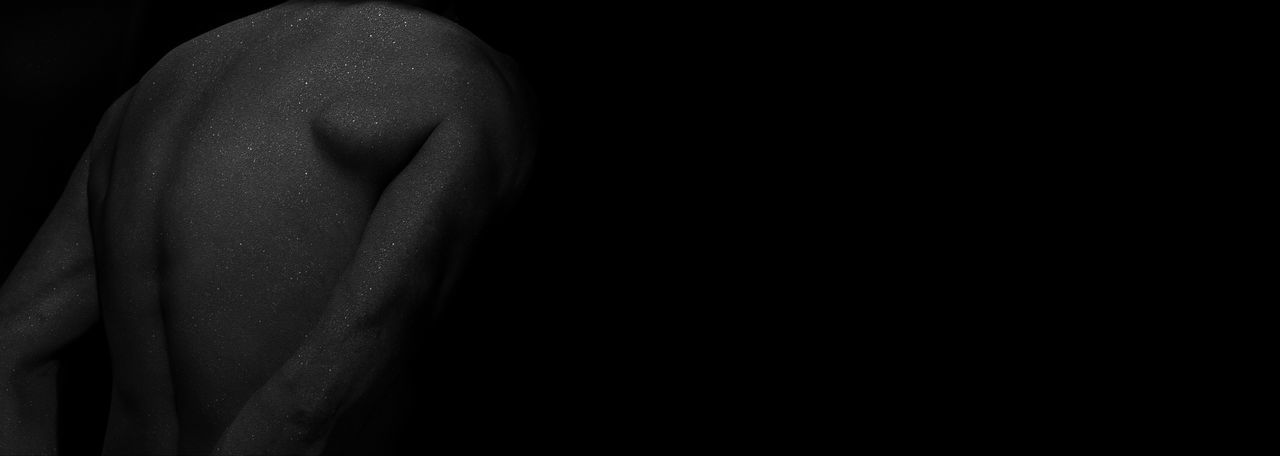 Close-up of shirtless man against black background