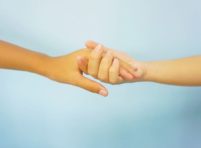 Midsection of couple holding hands against white background