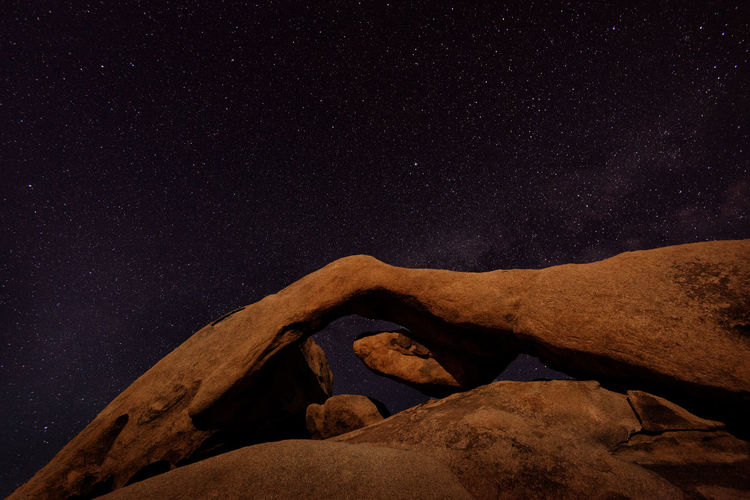 Low angle view of rock against sky at night