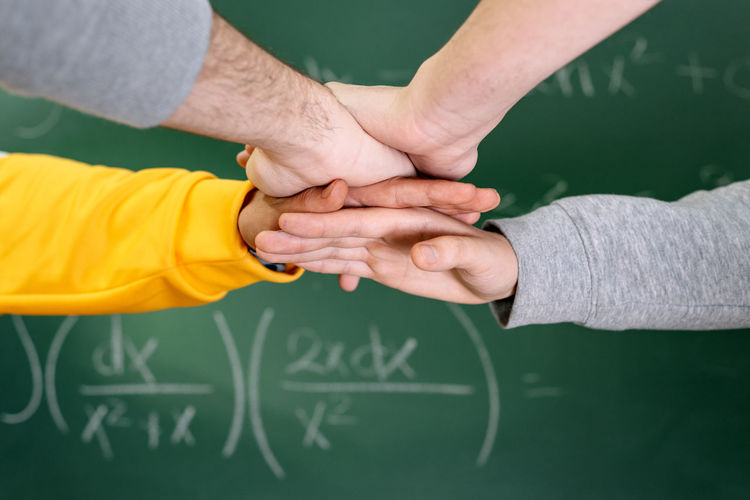 Cropped image of people stacking hands