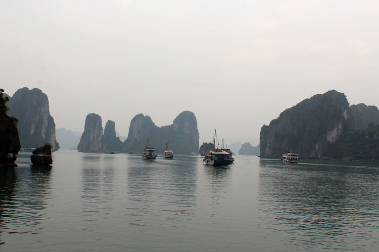 Boats On Halong Bay By Rock Formations Against Clear Sky