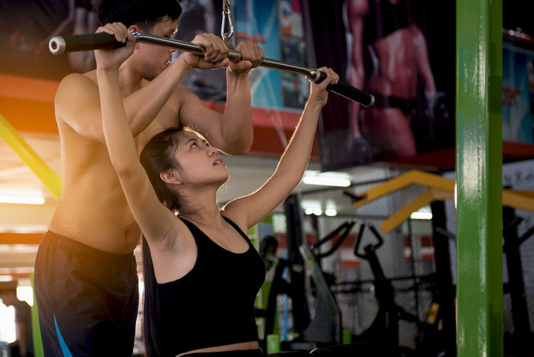 Man assisting young woman in exercising at gym